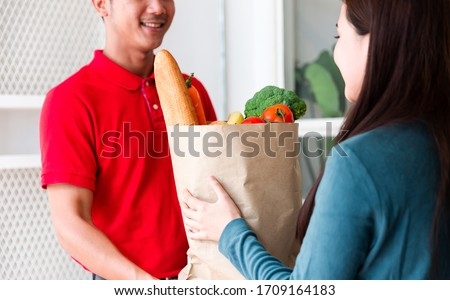 Woman receiving fresh food in paper bag or paper container from delivery man at the door. Postman delivery packet of food, vegetable to recipient at home. Food delivery, shopping online and transport #1709164183