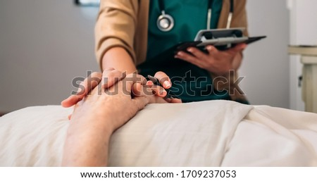 Unrecognizable young female doctor comforting unrecognizable older female patient #1709237053