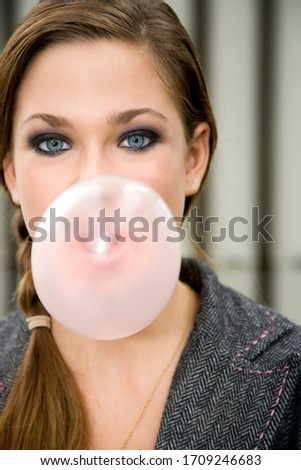 A teenage girl blowing bubble gum #1709246683