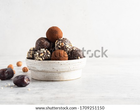 Energy balls. Healthy raw dessert (bliss balls), vegetarian truffles, sugar free candies made of dates, hazelnuts, cocoa powder. Step by step cooking. White wooden background.  Royalty-Free Stock Photo #1709251150
