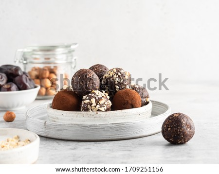 Energy balls. Healthy raw dessert (bliss balls), vegetarian truffles, sugar free candies made of dates, hazelnuts, cocoa powder. Step by step cooking. White wooden background.  Royalty-Free Stock Photo #1709251156