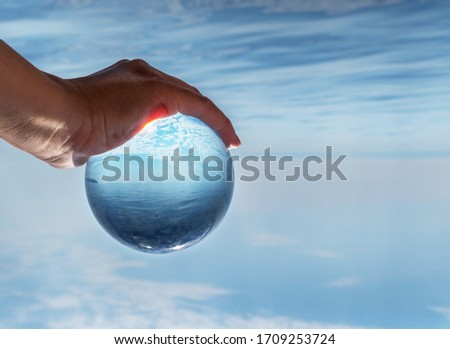 Crystal ball in the man's hand. Original upside down view and rounded perspective of the sky and sea. Original and engaging picture.