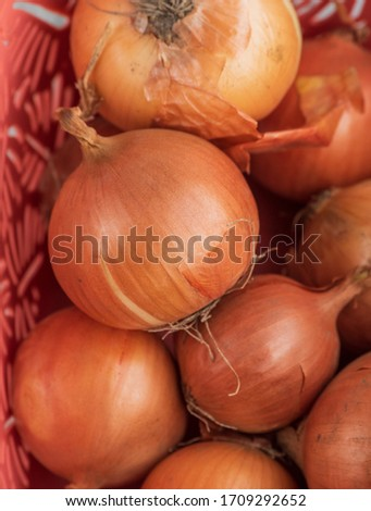 onion. Onions in a basket. Large onion harvest in a basket. Bulb onion is rich in vitamins, useful spring. Onion peel on a wooden background. Large onions can be seen from above.Raw onions in a basket #1709292652