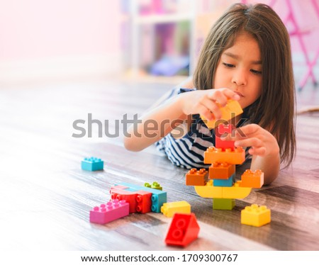 Portrait of a cute happy little preschool Hispanic girl playing alone with colorful construction blocks in her bedroom floor at home. Child Developing Motor Skills With Games Copy Space