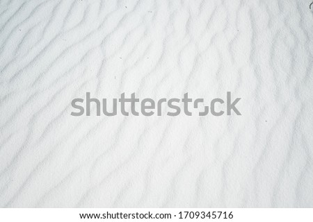 Wavy texture of white sands blown in the wind.