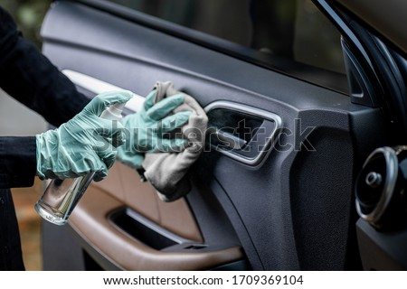 Car disinfecting service. Woman disinfecting and cleaning the inside handle of the car door. Safety and preventing infection of Covid-19 virus, contamination of germs or bacteria, wipe clean surfaces Royalty-Free Stock Photo #1709369104