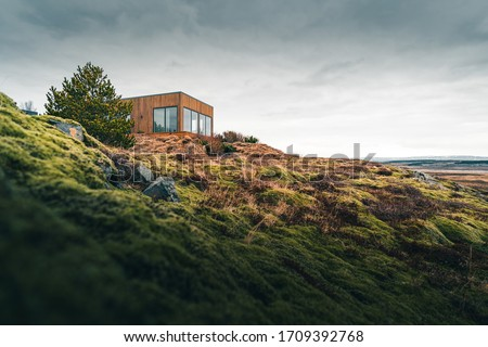 A tiny house on a grassy hill perfect for isolated vacation or just a peaceful relax in the connection with nature. Modern architecture in the Scandinavian countries Royalty-Free Stock Photo #1709392768