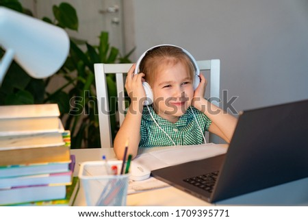 small girl with blond hair in a green dress in headphones listens to music, an audio lesson on the laptop. the social distance. quarantine and epidemic. #1709395771