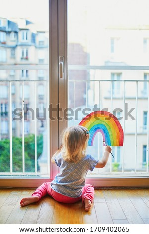 Adorable toddler girl painting rainbow on the window glass as sign of hope. Creative games for kids staying at home during lockdown. Self isolation and coronavirus quarantine concept #1709402065