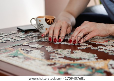 Woman hands with red nail polish putting jigsaw puzzle pieces together. Stay at home concept. Home quarantine. Coronavirus outbreak and family concept. Royalty-Free Stock Photo #1709407681