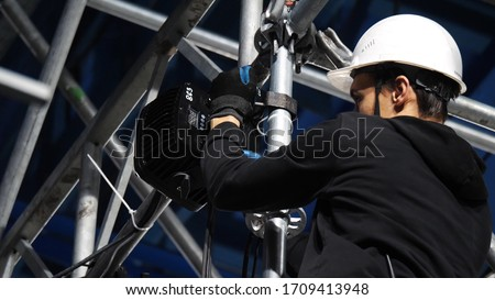 Close up of lighting technician installing professional lighting equipment for concert stage. Stock footage. Installation of led lights and projectors for the event. #1709413948