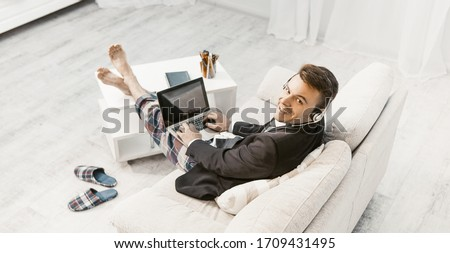 Businessman Works From Home, Cheerful Freelancer In Headphones, Man In Business Jacket And Pajama Pants Sits On Sofa Looking At Camera While Using Computer, Toned Image, High Angle View #1709431495