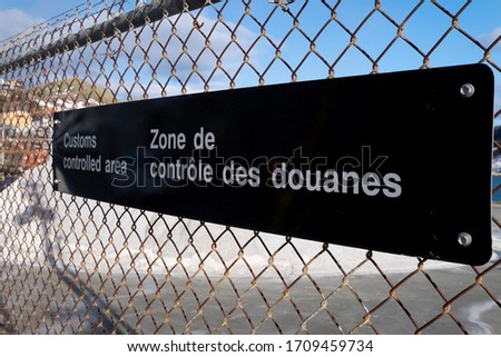 A black and white sign in English and French which says customs restricted area and zone de controle des douanes. The sign is attached to a wire yard fence with colourful buildings in the background.