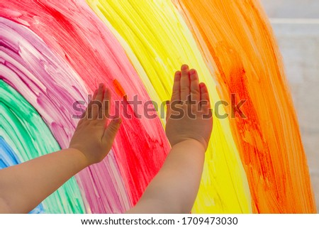 Child's hands touch painting rainbow on window. Playtime during covid-19 pandemic. Concept of hope. Family life background. kids leisure at home, safety joy symbol