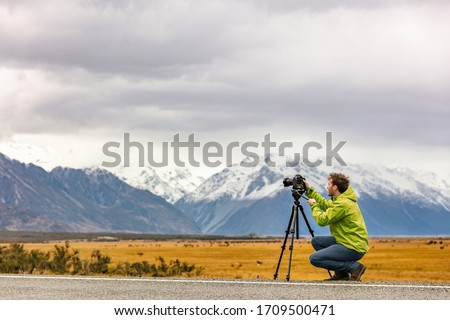 Tourist photographer taking pictures with professional camera on tripod on adventure travel vacation in New Zealand mountains landscape.