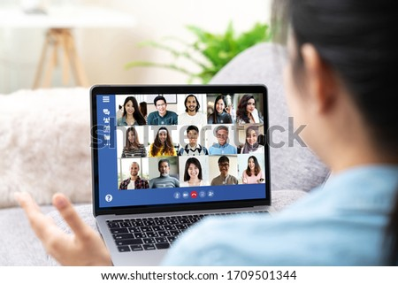 Back view of young asian business woman work remotely at home video conference remote call to corporate group. Meeting online,videocall, group discuss online concept with screen of teamwork on laptop. #1709501344