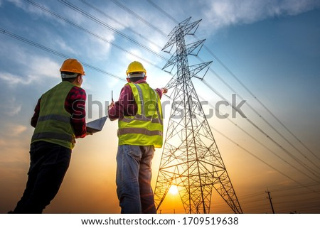 Picture of two electrical engineers using a notebook computer standing at a power station to view the planning work by producing electrical energy at high voltage electrodes. Royalty-Free Stock Photo #1709519638