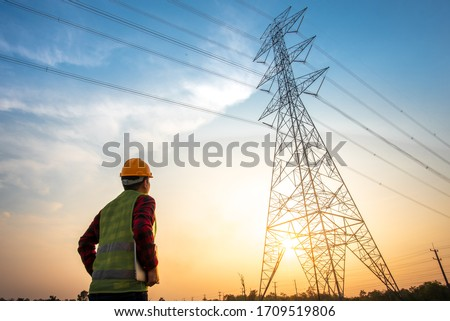 Picture of an electrical engineer standing and watching at the electric power station to view the planning work by producing electricity at high voltage electricity poles. #1709519806