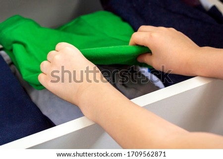 A litle boy's hands choosing and picking his clothes from a white chest. Wardrobe with child's clothing. Kid put his clothes in closet. Artificial noise, selective focus, backlight #1709562871