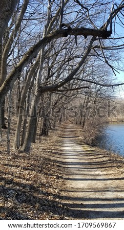 Trail along the Skunk River in Ames, IA taken in early spring. Blue water, bare trees, weathered hiking path, and old fall leaves pictured.