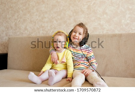 children learn english with headphones. Two girls listen to music on headphones