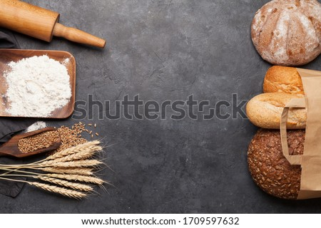 Various bread with wheat, flour and cooking utensils on stone table. Top view flat lay with copy space #1709597632