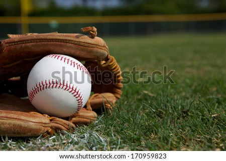 New Baseball in a Glove in the Outfield Royalty-Free Stock Photo #170959823
