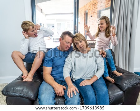 COVID-19 Isolation and mental health. Stressed out parents struggling with having the children at home during Coronavirus lockdown. Mother and father coping with anxious kids fighting in quarantine. #1709613985