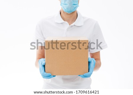 home delivery, online order. A man in uniform, a medical mask and rubber gloves with a box, a parcel in his hands. Food and food delivery during the quarantine of the coronavirus pandemic #1709616421