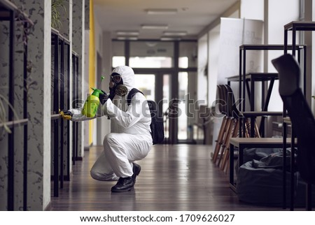 Cleaning and Disinfection at town complex amid the coronavirus epidemic. Professional teams for disinfection efforts. Infection prevention and control of epidemic. Protective suit and mask #1709626027
