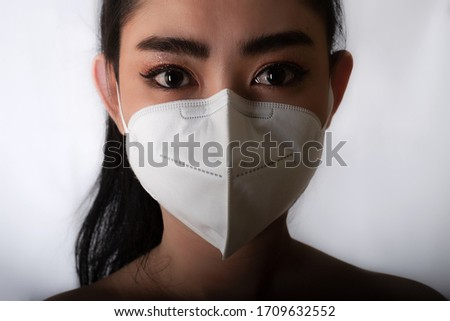 Close up of young Asia woman putting on a medical mask n95 to protect from airborne respiratory diseases as the flu covid-19 PM2.5 dust and smog at gray background, Safety virus infection concept #1709632552