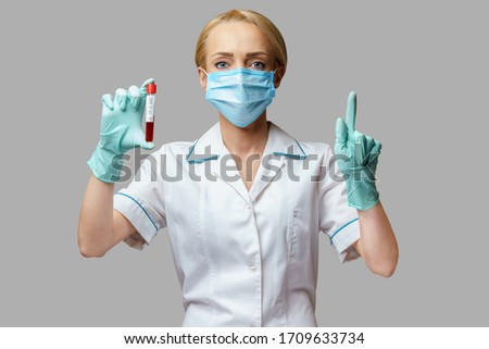 medical doctor nurse woman wearing protective mask and gloves - holding virus blood test #1709633734