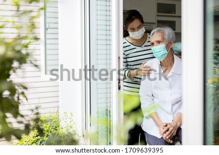 Caregiver woman take care of the elderly,depressed senior is waiting for her family to visit at home,social distancing,nostalgia,stress,life depression,stay home during Covid-19,Coronavirus pandemic   #1709639395