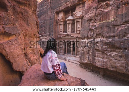 A woman traveler sitting at viewpoint of Petra ancient city looking at the Treasury or Al-khazneh, Jordan, Arab, Asia #1709645443