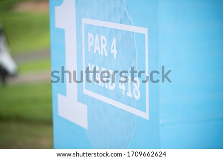 A sign for the golf game in a sports competition. A golf course sign showing yard and par.