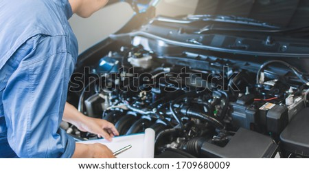 Asian Man mechanic inspection writing note on clipboard.Blue car for service maintenance insurance with car engine.for transport automobile automotive image. Royalty-Free Stock Photo #1709680009
