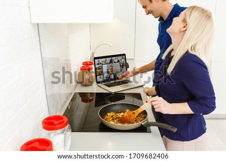 A woman cooking and using the laptop in the kitchen #1709682406