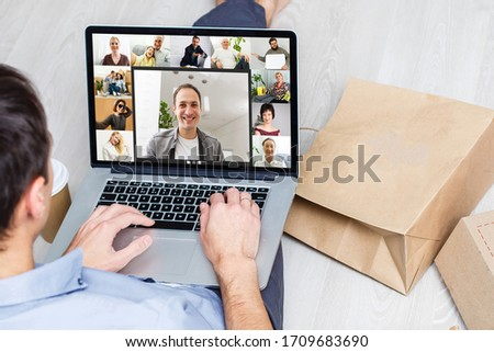 Back view of young man using headset and laptop and having videoconference at home #1709683690
