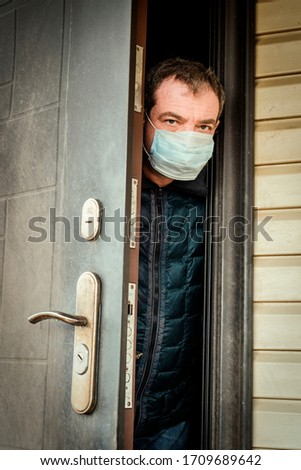 A man in a medical mask on the threshold of his house. Coronavirus Quarantine Isolation #1709689642