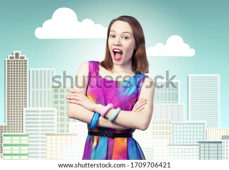 Joyful caucasian woman standing with folded arms. Elegant fashionable lady in colorful dress on background cartoon cityscape. Good looking redhead girl with open mouth. Pretty female student posing #1709706421