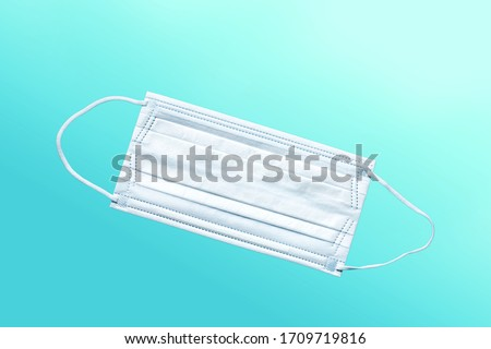simple white air protection mask on blue background. Disposable surgical face mask cover the mouth and nose. Healthcare and medical concept. #1709719816