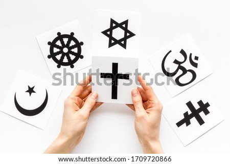 Choose religion concept. Hand with catholic cross near world religions symbols on white background top view Royalty-Free Stock Photo #1709720866