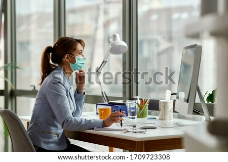 Young businesswoman wearing face mask while working on a computer in the office.  #1709723308