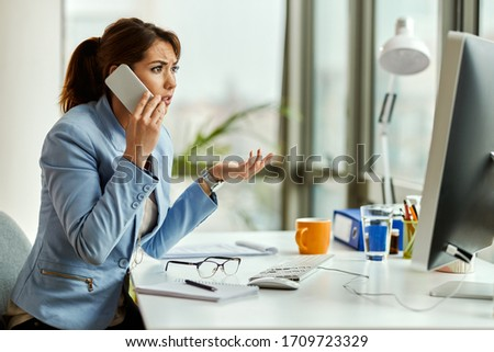 Young displeased businesswoman communicating over mobile phone while working on a computer in the office.  #1709723329