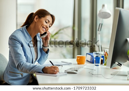 Young happy businesswoman talking on mobile phone and taking notes in the office.  #1709723332