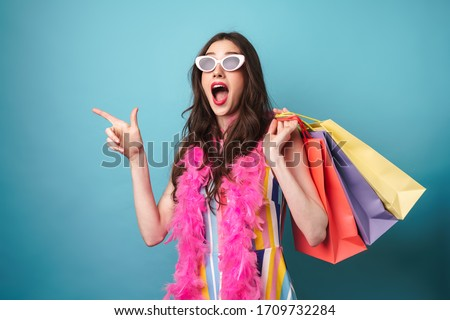 Photo of surprised young woman holding shopping bag and pointing finger aside isolated over blue wall #1709732284