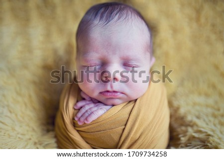 newborn sleeping baby boy or girl picture like newborn potato in yellow wrap on furry blanket background