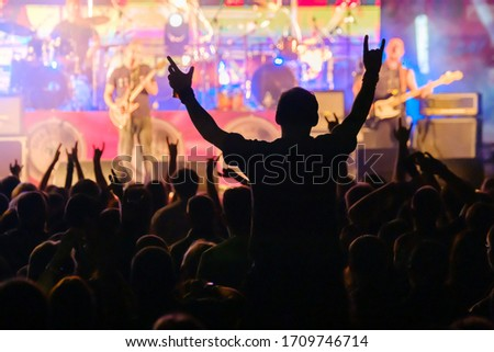 Fans at live rock music concert cheering musicians on stage, back view Royalty-Free Stock Photo #1709746714