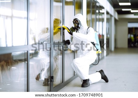 Man in protective hazmat suit washes door handles in office to preventing the spread of coronavirus, pandemic in quarantine city. Cleaning and disinfection of office. Covid-19. #1709748901