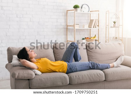 Stay home, stay peaceful. Happy millennial woman lying on sofa and relaxing indoors #1709750251